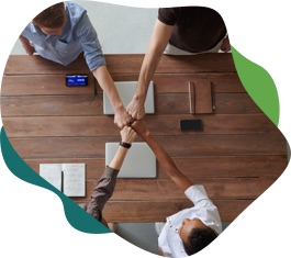 Top-down view of people fist-bumping over a conference table