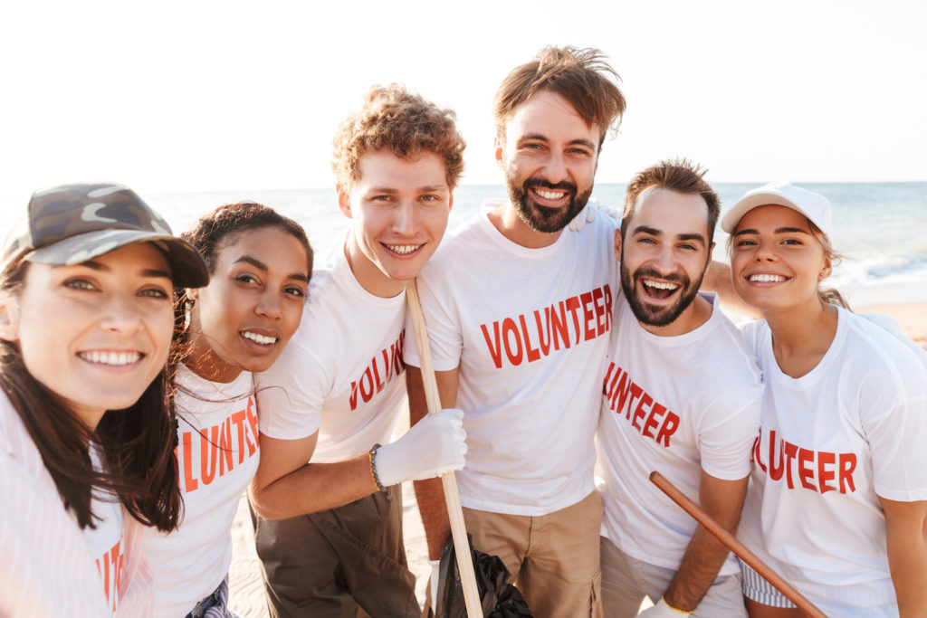 Photo of joyful eco volunteers people smiling at camera together while cleaning beach from plastic trash